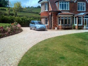 Gravel driveway landscaped into the lawn