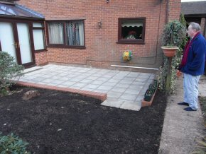 This area is landscaped using a retaining wall around a patio area. We have also put in Aco drainage Channels leading to a soak away.