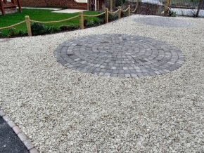Granite set rotund in driveway with a gravel surround, edged by a Post and Rope Trip fence in Watchet.